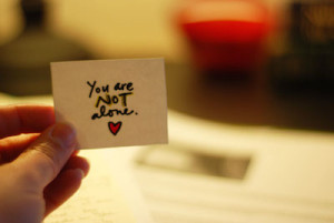 "picture of a hand, holding a white card, with the words ""You Are Not Alone"" printed on it."