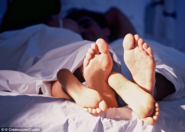 the feet of a couple in bed together.