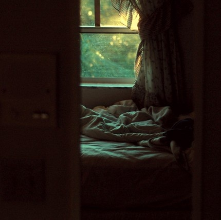 a soft focus of a bedroom, with open window and soft light, with rumpled sheets from not sleeping
