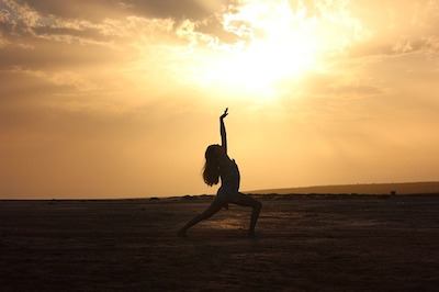 a woman dancing on the beach at sunset in yogic poses