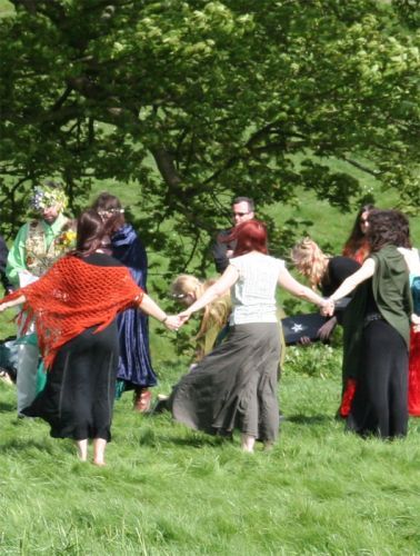 A group of pagan worshipers praying together in a circle in England.