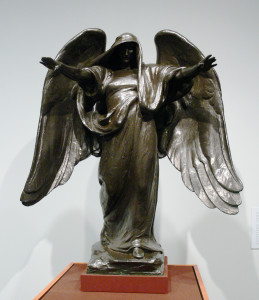 A bronze statue of an angel wearing a hood, offering a pose of benediction during prayer.