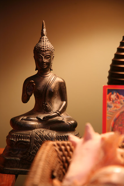 Buddha in prayer or altar area, offering a benediction pose.
