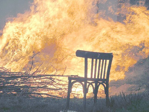 a table chair sitting next to a wild fire, ablaze
