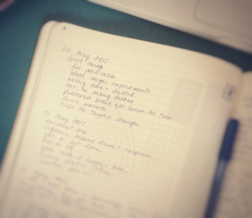 an open journal with a pen and writing across the page
