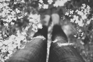 colorless photo of a woman in jeans in a thicket of cherry blossoms