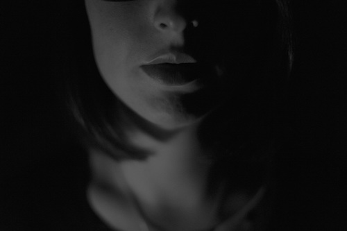 lower half of face and neck of a woman in shadows