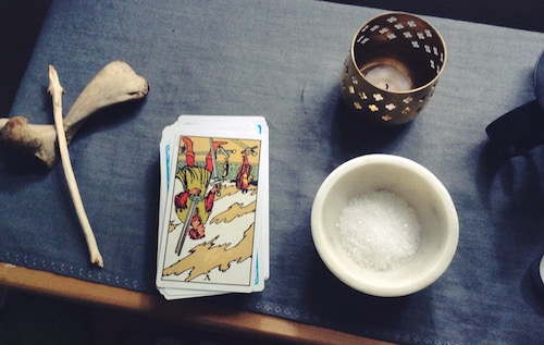 The tarot card, The Five of Swords, upside down on a table with a candle and a bowl of salt