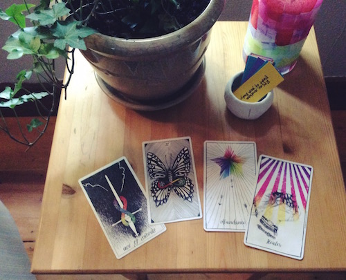 a table with two tarot cards and two oracle cards on it with a plant and a small cup nearby
